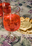 Wine and Cheese. Pair of wine glasses with rose  wine, cheese and crackers on floral tablecloth Royalty Free Stock Photography