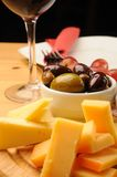 Wine and Cheese. Olives, cheese and a glass of red Wine on a wooden restaurant table stock photos