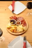 Wine and Cheese. Olives, cheese and a glass of red Wine on a wooden restaurant table royalty free stock images