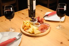 Wine and Cheese. Olives, cheese and a glass of red Wine on a wooden restaurant table stock photography
