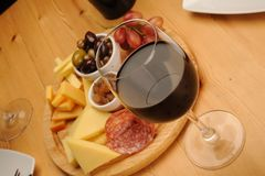 Wine and Cheese. Olives, cheese and a glass of red Wine on a wooden restaurant table royalty free stock photography