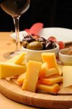 Wine and Cheese. Olives, cheese and a glass of red Wine on a wooden restaurant table stock photo