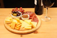 Wine and Cheese. Olives, cheese and a glass of red Wine on a wooden restaurant table royalty free stock image