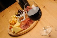 Wine and Cheese. Olives, cheese and a glass of red Wine on a wooden restaurant table royalty free stock photos