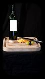 Wine and cheese. On a wooden board.  Wine label left blank for text.  Isolated against a black background Stock Photo