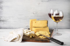 Wine and cheese. Assorted cheese with olives on board and glasses of red and white wine on rustic wooden background Stock Photography