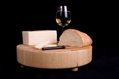 Wine Cheese and Bread. Close up image of a block of cheese with a half loaf of French bread and a chilled glass of white wine atop a hardwood cutting board Royalty Free Stock Photo
