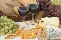 Wine, cheese, bread and grape. Wine glasses and various food cheese grape bread and other Stock Photos