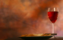 Wine, Cheese, and Crackers. Glass of wine, plate of cheese and crackers with romantic atmosphere Stock Photo