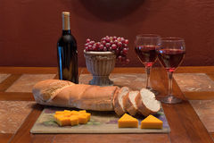 Wine and Cheese. Romantic ambience setting with red wine, grapes in an Italian vase, bread & cheese Stock Photo