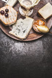 Wine and cheese on dark rustic background, top view Royalty Free Stock Photo