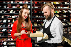 Wine and cheese degustation. Young women with glass of wine choosing cheese during the degustation with sommelier or seller at the restaurant or food market royalty free stock photography