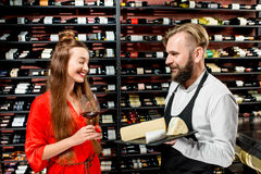 Wine and cheese degustation. Young women with glass of wine choosing cheese during the degustation with sommelier or seller at the restaurant or food market royalty free stock images