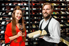 Wine and cheese degustation. Young women with glass of wine choosing cheese during the degustation with sommelier or seller at the restaurant or food market royalty free stock photo