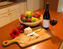 Wine and Cheese-1. Display of a fine bottle and glass of wine with cheese crackers and fruit Royalty Free Stock Photos