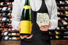 Wine and cheese. Food seller holding a bottle of white wine and a pieace of blue cheese. Choosing wine according to the type of cheese. Bottle with empty label royalty free stock images