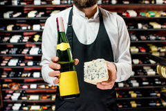 Wine and cheese. Food seller holding a bottle of white wine and a pieace of blue cheese. Choosing wine according to the type of cheese. Bottle with empty label royalty free stock photography