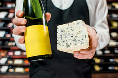 Wine and cheese. Food seller holding a bottle of white wine and a pieace of blue cheese. Choosing wine according to the type of cheese. Bottle with empty label stock photos