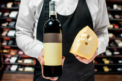 Wine and cheese. Food seller holding a bottle of white wine and a pieace of gouda cheese. Choosing wine according to the type of cheese. Bottle with empty label stock images