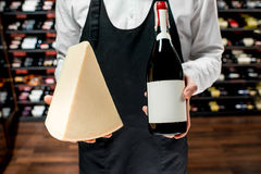 Wine and cheese. Food seller holding a bottle of white wine and a pieace of parmegiano cheese. Choosing wine according to the type of cheese. Bottle with empty stock images