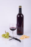 Wine and cheese. Wine in a glass, a bottle of wine, corkscrew and cheese Stock Photos