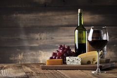 Wine and cheese. Glass of red wine, cheese and grapes on old wooden table. Old wooden background royalty free stock image