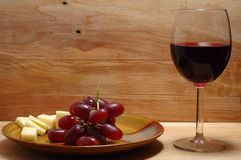 Wine, cheese and grape. Glass of wine close to plate fool of grape and cheese Royalty Free Stock Photo