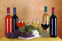 Wine, cheese and grapes. Bottles of red wine, white wine and rose wine with typical Italian cheese and grapes Royalty Free Stock Image