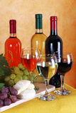 Wine, cheese and grapes. Bottles of red wine, white wine and rose wine with typical Italian cheese and grapes Royalty Free Stock Photography