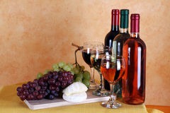 Wine, cheese and grapes. Bottles of red wine, white wine and rose wine with typical Italian cheese and grapes Royalty Free Stock Photos