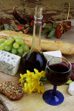 Wine, cheese, grapes and herbs. Romantic dinner with cheese, wine, grapes and jonquils on rustic board Stock Photos