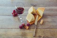 Wine, cheese and grapes on wooden table Stock Photography