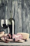 Wine, Cheese and Meat vintage photo. Wine, cheese and meat on a wooden rustic table, food vintage background Royalty Free Stock Images