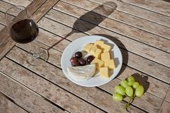 Wine, cheese, olives and grapes stock photography