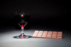 Wine and chocolate. Soft dreamy image of a glass of red wine and. Wine and chocolate. Soft focus dreamy image of a glass of red wine and bar of chocolate Stock Images