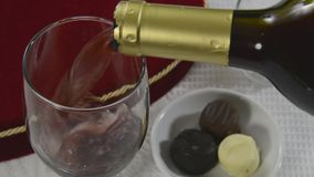 Wine and chocolates. Pouring red wine by a heart shaped box of chocolates stock footage