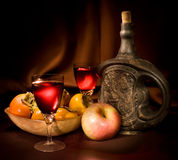 Wine with clay bottle, persimmon and apple stock images