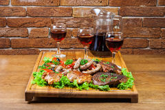 Wine and cold cuts on a wooden board Royalty Free Stock Image