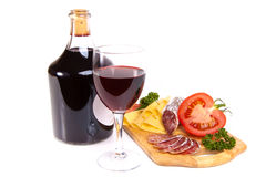 Wine and cold snacks. Bottle of wine with salami, cheese and tomato on wooden board isolated on white Stock Photo