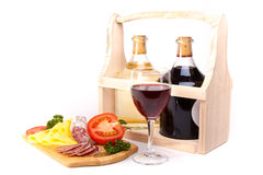 Wine and cold snacks. Bottle of wine with salami, cheese and tomato on wooden board isolated on white Stock Image