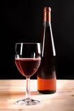 Wine collection: Rose wine glass and bottle on wooden table Stock Photography