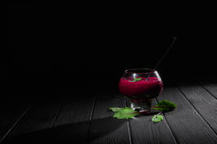 A wine-colored beet smoothie dessert. A big transparent glass filled with thick vegetable cocktail on a black background Royalty Free Stock Image
