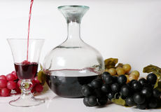 Wine composition. Wine poured in a glass with grapes around in a composition on a white background Stock Photo