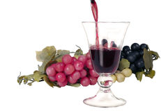 Wine composition. Wine poured in a glass with grapes around in a composition on a white background Stock Photography