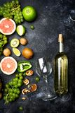 Wine concept. Bottle and glass of young white bio wine with green grapes, grapefruit and other fruit on a gray stone background stock photo