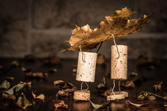 Wine cork figures, Concept two men carry a leaf Royalty Free Stock Photo