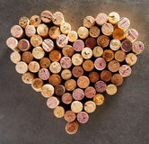Wine corks arranged into shape of heart. Against dark background Stock Images