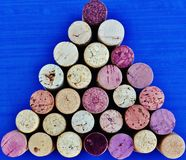 Wine corks arranged in a triangle. Used wine corks arranged in a triangular pattern against a blue background Stock Photo