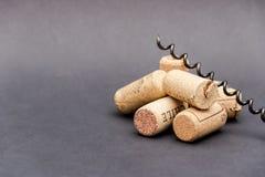 Wine corks with corkscrew on black background. Free copy space.