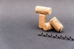 Wine corks with corkscrew on black background. Free copy space